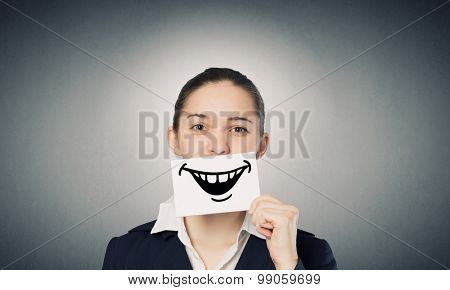 Pretty young girl holding white card with drawn smile with teeth