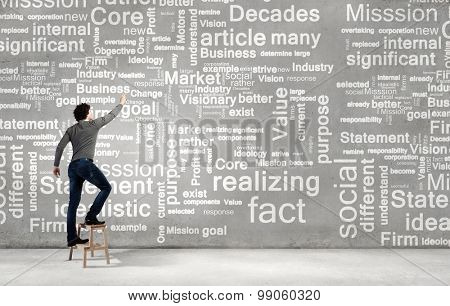 Young businessman standing with back and writing different words on wall