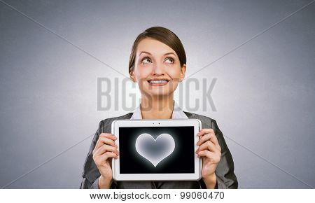 Beautiful young woman holding tablet pc with love heart