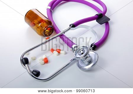 Pills ,tablets and stethoscope on white background