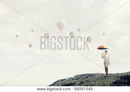 Young pretty businesswoman with rainbow colorful umbrella