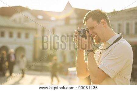 Tourist with photo camera shooting on the street under sunlight