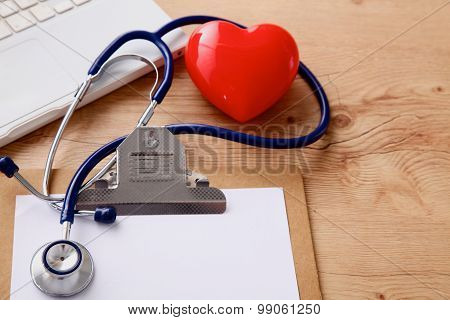 Medical stethoscope lying on a computer keyboard, documents