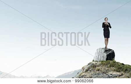 Cheerful businesswoman standing on rock top and playing fife