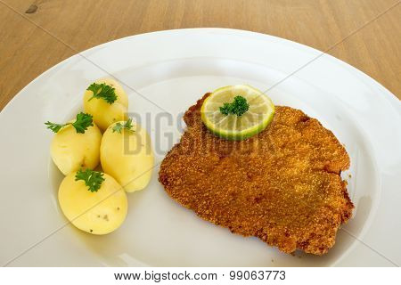 breaded cutlet with parsley potatoes on a plate