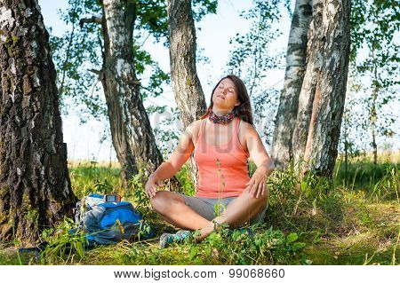 Young woman hiker meditate in a forest