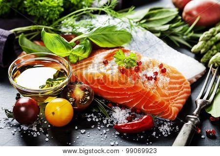 Delicious  portion of fresh salmon fillet  with aromatic herbs, spices and vegetables - healthy food, diet or cooking concept