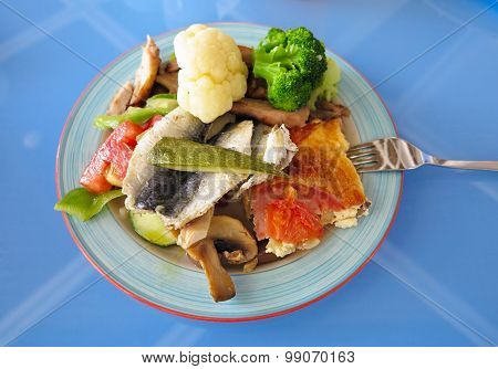 Fish And Vegetables On Dish Over Blue Table