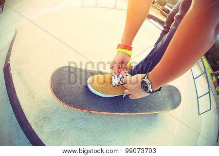 young asian skateboarder tying shoelace on skateboard