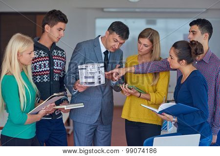 group of students working with teacher on wooden small house model