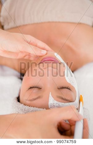 Upward view of an attractive young woman receiving treatment at spa center