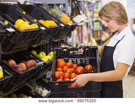 Smiling staff woman holding a box with fresh vegetables at supermarket