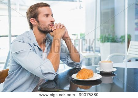 Young thoughtful man looking in the distance in the cafe