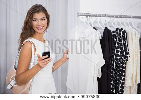 Portrait of smiling woman using smartphone at a boutique