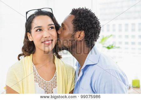 Portrait of a man kissing his colleague in the office