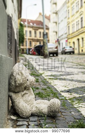 Old Teddy Bear On The Sidewalk In The City