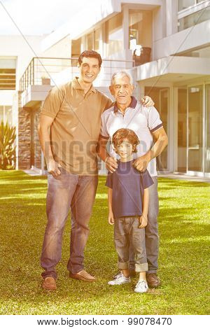 Family with grandfather and grandchild in front of a house in the garden