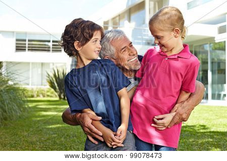 Grandfather having fun with his two grandchildren in a garden in front of a house