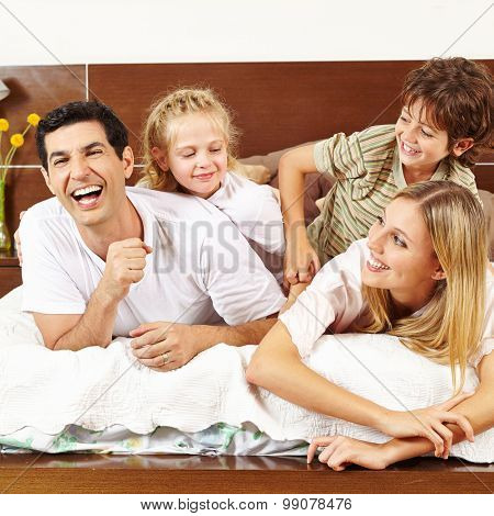 Two children tickling their parents in bed in the morning