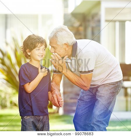 Grandfather whispering a secret in the ear of his grandson in a garden