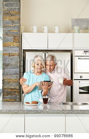 Senior couple with tablet computer in kitchen at breakfast