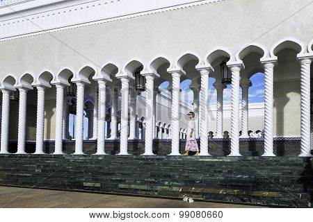 Woman walking on territory of white Mosque