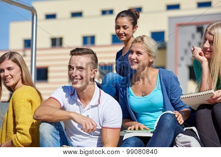 Group portrait  of happy  students outside sitting on steps have fun