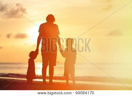 father and two kids walking on sunset beach