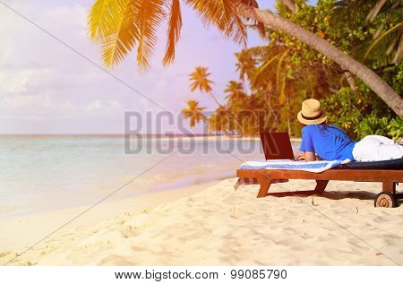 young man with laptop on tropical beach