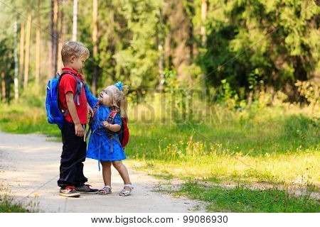 happy little boy and girl with backpacks in summer