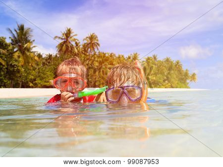father and son snorkeling on tropical beach