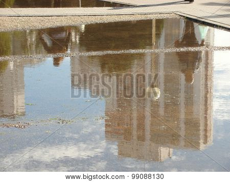 Building and people reflected on a pond