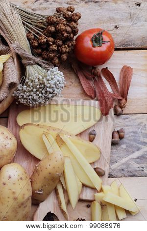 Potato Chip And Fresh Potatoes On Wood Background