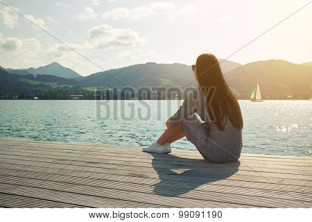 young woman sitting on the moorage and looking at beautiful view