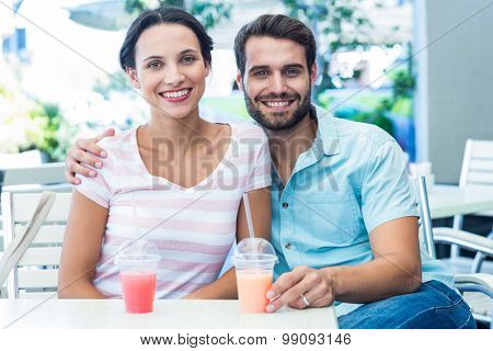 Happy couple drinking milkshakes together in a cafe