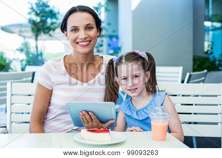 Mother and daughter using tablet computer together in a restaurant