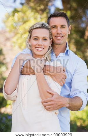 Portrait of smiling couple embracing in parkland
