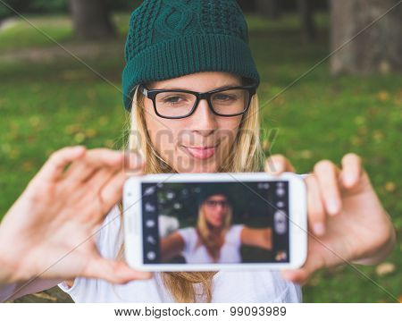 Blonde woman posing outdoor, taking self portrait
