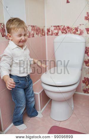 little boy looks in toilet