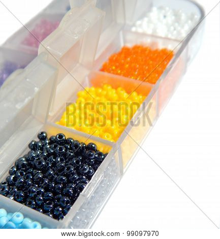Black, yellow, orange, white, blue beads in boxes on a white background, closeup