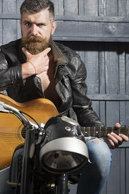 picture of moustache  - Pensive young musical man with beard and handlebar moustache in leather jacket sitting on motorcycle with acoustic guitar in garage on wooden wall background vertical picture - JPG
