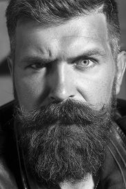 foto of long beard  - Closeup of handsome serious unshaven male emotional face with long beard and handlebar moustache looking forward on workshop background black and white vertical picture - JPG