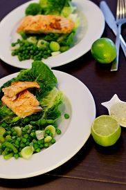 stock photo of sweet pea  - Delicious Roasted Salmon with Sweet Pea Leek and Salad Romano on White Plates closeup on Dark Wooden background - JPG