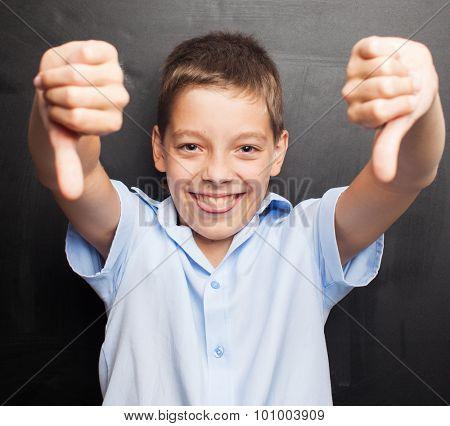 Teenager near blackboard showing dislike. Child at school. Student at classroom