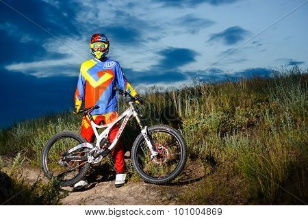 ZAPORIZHZHYA, UKRAINE - JUNE 16, 2015: Fully Equipped Professional Downhill Cyclist with Bike on the Night Rocky Trail. Extreme Sports