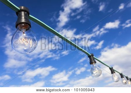 Blue sky thinking light bulb moment concept chain of filament bulbs