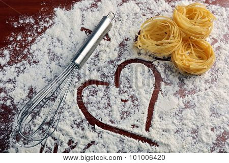 Row pasta with corolla on flour background