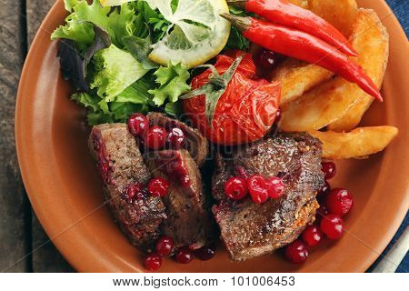 Tasty roasted meat with cranberry sauce, salad and roasted vegetables on plate, close-up