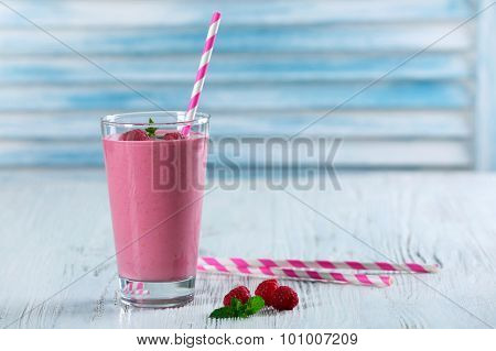 Glass of raspberry milk shake with berries on wooden background