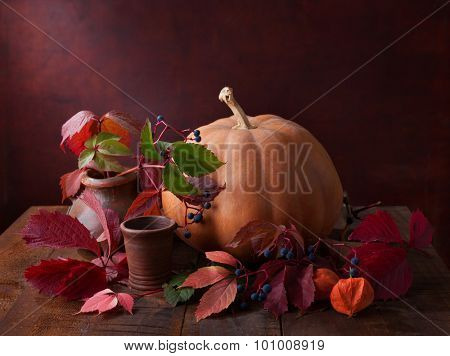 Autumn still life - pumpkin, autumn leaves and physalis on  old wooden table.
